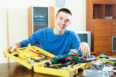 Happy guy doing something with toolbox in home Royalty Free Stock Image