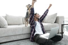 Happy guy exults with his dog sitting near the sofa in the living room. The concept of home life Royalty Free Stock Images