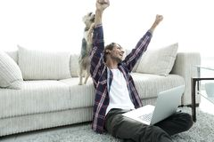 Happy guy exults with his dog sitting near the sofa in the living room. The concept of home life Royalty Free Stock Photo