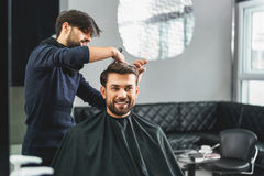 Happy guy getting haircut by hairdresser Royalty Free Stock Image