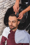 Happy guy getting hairwash at beauty salon. Calm young man is enjoying washing of his hair by hairdresser. His eyes are closed with pleasure Royalty Free Stock Image