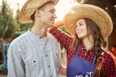 Happy guy and girl gardeners in a straw hats look at each other in the garden on a sunny day. royalty free stock photos