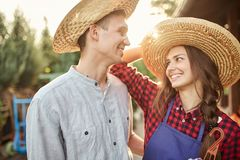 Happy guy and girl gardeners in a straw hats look at each other in the garden on a sunny day. royalty free stock image