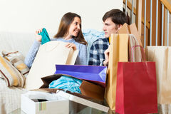 Happy guy and girl looking at purchases. In home Stock Photography