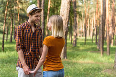 Happy guy and girl resting in forest Stock Image