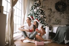 Happy guy and girl in white t-shirts and Santa Claus hats sit with red cups on the floor in front of the window next to stock photography