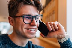 Happy guy has phone conversation at cafe Royalty Free Stock Images