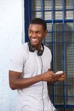 Happy guy with headphones and mobile phone Royalty Free Stock Photos