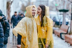 Happy guy and his girlfriend dressed in yellow raincoats are walking on the street in the rain royalty free stock photography