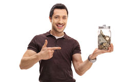 Happy guy holding a jar filled with money and pointing Royalty Free Stock Photos