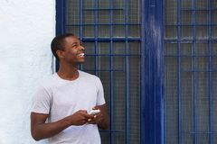 Happy guy holding mobile phone and looking away Stock Image