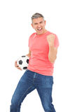 Happy guy holding a soccer ball Royalty Free Stock Image