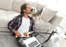 Happy guy with laptop jubilant in spacious living room. Concept of success Royalty Free Stock Photo