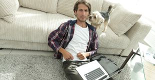 Happy guy with laptop jubilant in spacious living room. Concept of success Stock Images