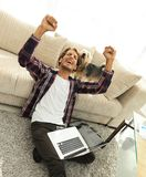Happy guy with laptop jubilant in spacious living room. Concept of success Stock Photo