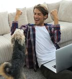 Happy guy with laptop jubilant in spacious living room. Stock Image