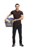 Happy guy with a laundry basket full of clothes Stock Photo