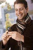 Happy guy looking at mobile phone Stock Photo