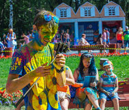 The happy guy looks at smartphone. The festival of colors Holi Royalty Free Stock Photography