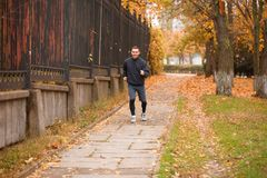A happy guy makes jog in the autumn park. The concept of sport. A happy young sports guy dressed in sportswear makes a light jog in the autumn park. The concept Royalty Free Stock Photo