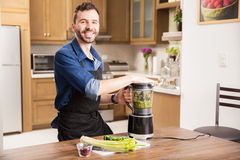 Happy guy making a green smoothie Royalty Free Stock Photos