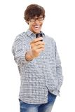 Happy guy making picture by phone. Young man laughing and filming something funny on his mobile phone. Isolated on white background, mask included Stock Images
