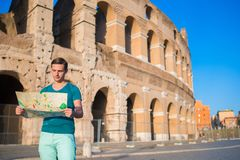Happy guy with map in front of Colosseum. Young man searching the attraction background the famous area in Rome, Italy Royalty Free Stock Image