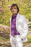 Happy guy in the park a white suit and purple Royalty Free Stock Photography