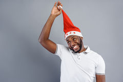 Happy guy playing with Christmas cap Royalty Free Stock Images