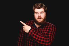 Happy guy is pointing up on a black background Stock Images