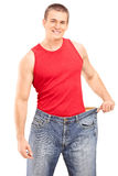 Happy guy posing in a pair of oversized jeans. Isolated on white background Stock Images