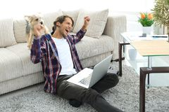 Happy guy rejoicing and raising his hands sitting near the sofa in the living room. Stock Photography
