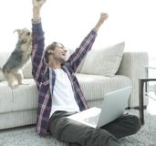 Happy guy rejoicing and raising his hands sitting near the sofa in the living room. Royalty Free Stock Images