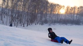 Happy guy rides and smiling snowtube on snowy roads.slow motion. snow winter landscape. outdoors sports stock footage