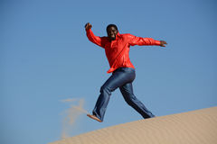 Happy guy running down dune. Full body of an African American young man with happy smiling facial expression jumping and running down a dune barefooted Stock Photography