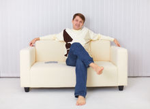 Happy guy sits on sofa and watches TV Stock Images