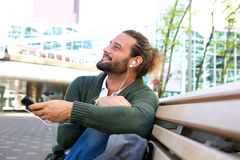Happy guy sitting on bench listening to music Royalty Free Stock Images