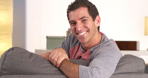 Happy guy sitting on couch Stock Images
