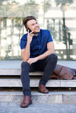 Happy guy sitting outside with cell phone Royalty Free Stock Image