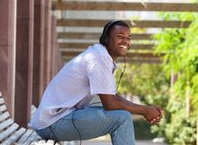 Happy guy sitting on park branch with headphones Stock Photography
