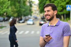Happy guy with smartphone smiling messaging outdoors Royalty Free Stock Images