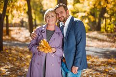 A guy hugs his mom in an autumn park. Happy guy with a smile in a suit hugging his mother`s coat with leaves in hands in an autumn park Royalty Free Stock Photo