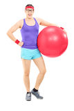 Happy guy in sportswear holding a fitness ball Royalty Free Stock Photos