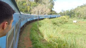 Happy guy standing in entrance of moving old blue train and smiling. Young man riding on passenger railway transport. Through beautiful nature landscape and stock video footage