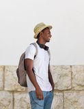 Happy guy standing outside with hat and bag Royalty Free Stock Images