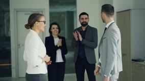 Happy guy in suit is getting job in company after successful interview, shaking hands and smiling expressing excitement