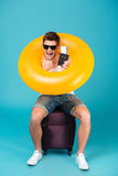 Happy guy in sunglasses sitting on a suitcase Royalty Free Stock Photo