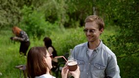Happy guy talks with girlfriend while drinking at picnic in the park