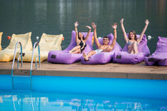 Happy guy and two attractive girls sitting on a cushioned lounger with his hands raised up and looking at the camera Stock Photography