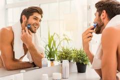 Happy guy using electric razor stock photos